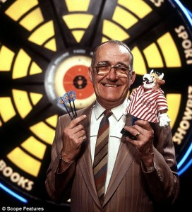 """Bullseye"" host Jim Bowen in front of the famous dartboard."